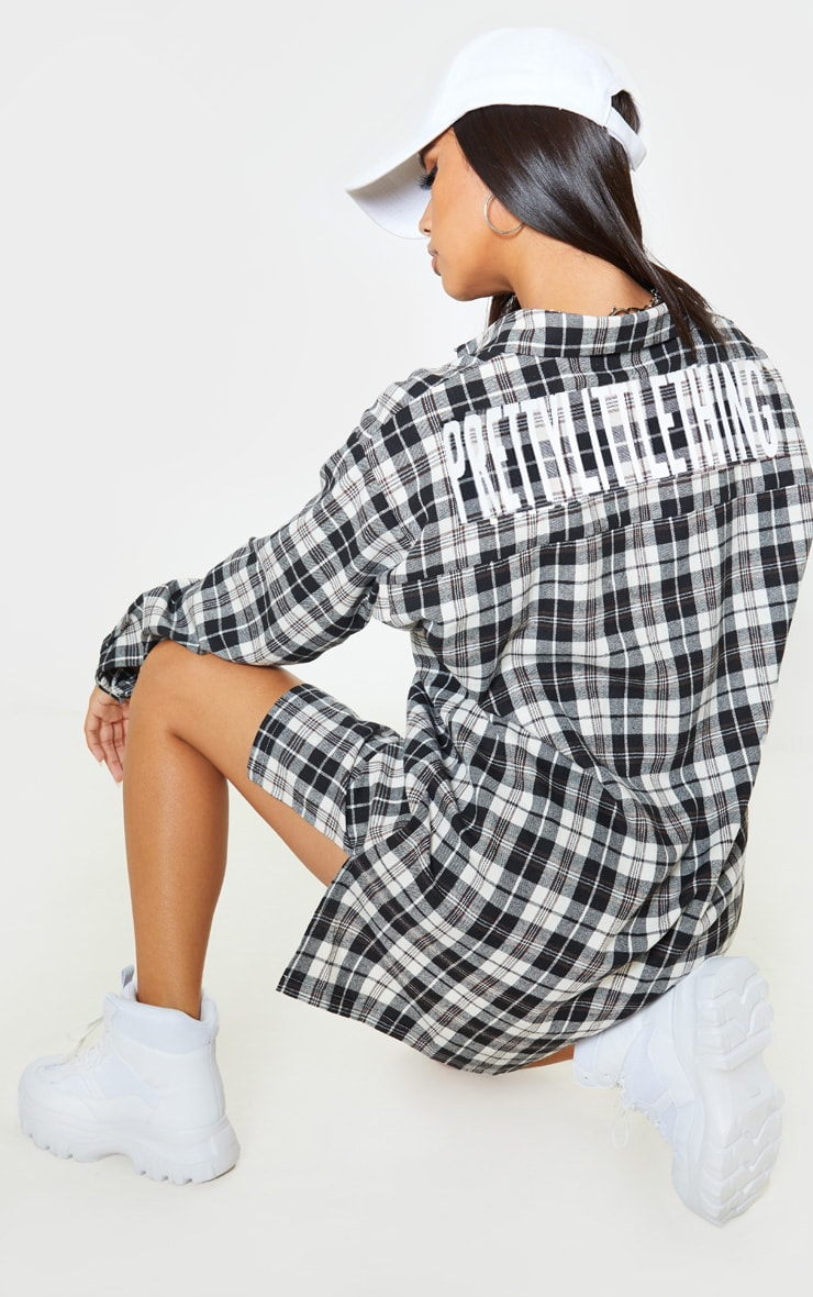 PRETTYLITTLETHING Black Slogan Checked Shirt Dress 1