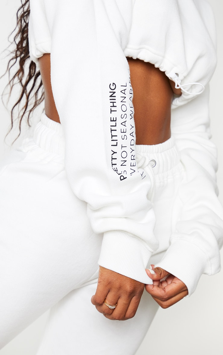 PRETTYLITTLETHING Shape Cream Slogan Printed Extreme Cropped Toggle Sweater 4