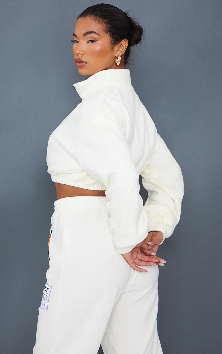 PRETTYLITTLETHING Cream Badge Detail Cropped Zip Through Fleece 2