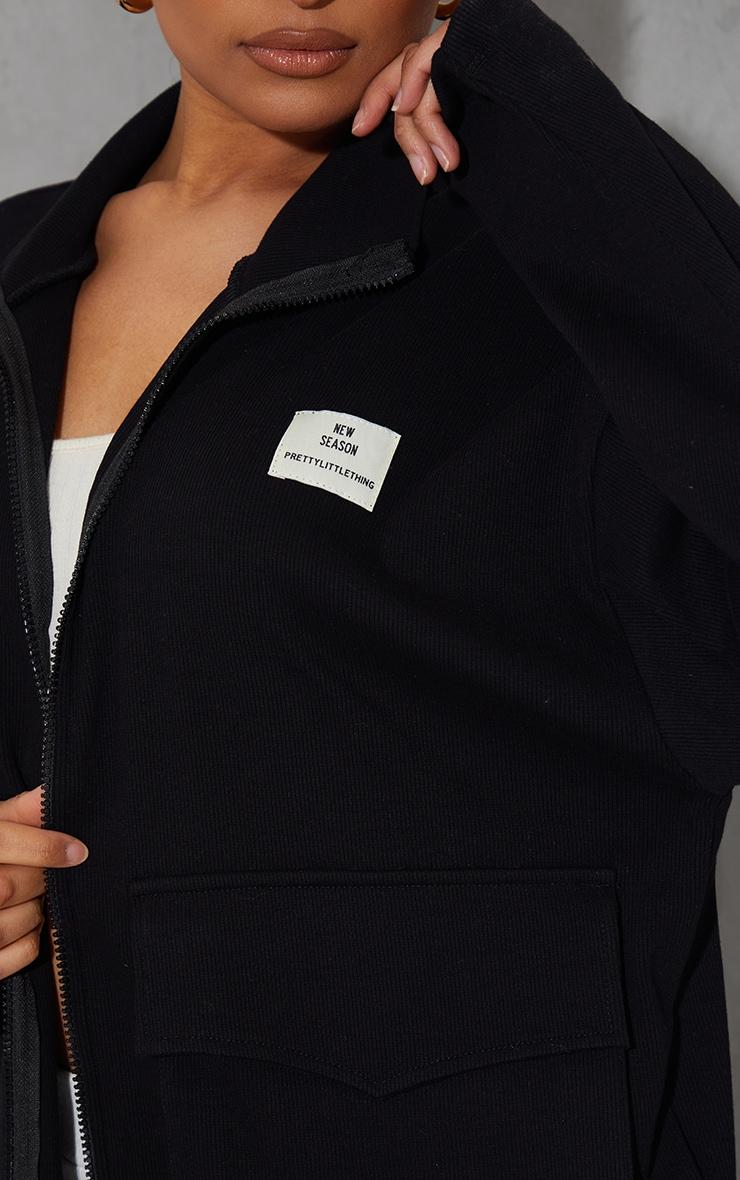 PRETTYLITTLETHING - Veste noire côtelée à poche devant et badge New Season 4