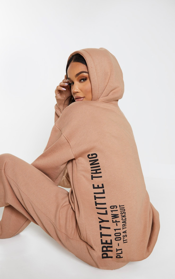 PRETTYLITTLETHING Mocha Oversized Slogan Back Pocket Front Hoodie 1