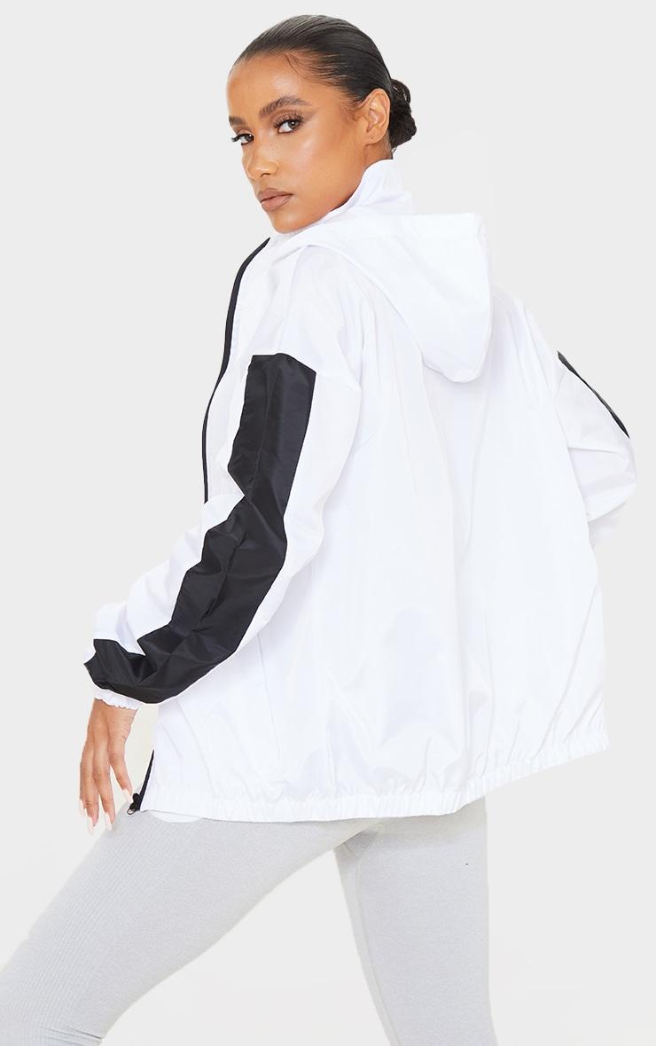 Veste style survêt blanche à capuche et parties contrastantes sur les manches 2