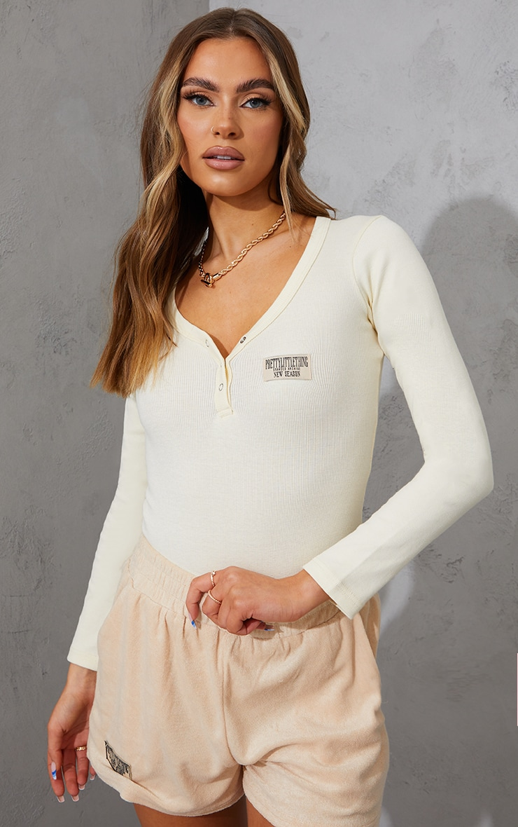 PRETTYLITTLETHING Cream Thick Rib Badge Detail Button Front Bodysuit