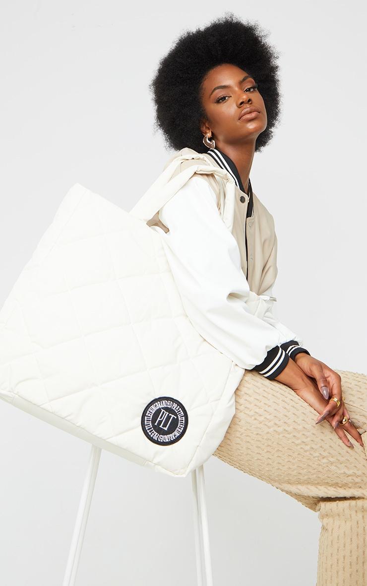 PRETTYLITTLETHING - Tote bag oversize en nylon matelassé crème à détail badge 1