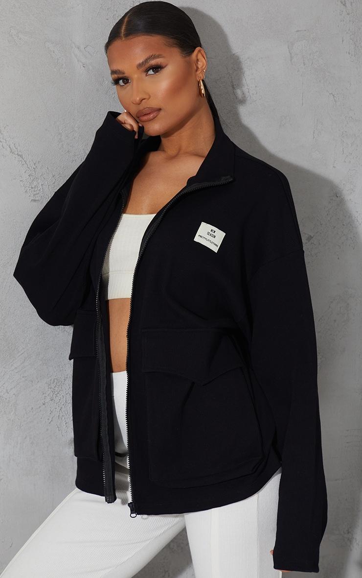 PRETTYLITTLETHING - Veste noire côtelée à poche devant et badge New Season 1