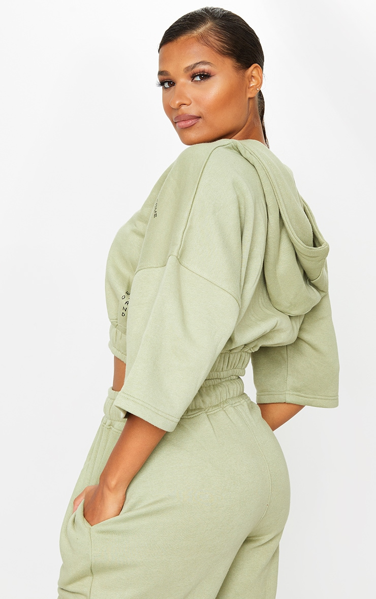 PRETTYLITTLETHING Olive Green Welcome To Our World Slogan Oversized Sleeve Zip Neck Cropped Hoodie 2